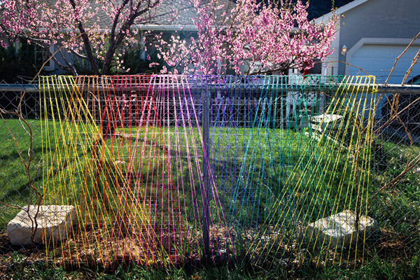 "Rainbow yarn stretched in triangular shapes on supports in a front yardGranary Arts ""Lawn Gnomes 2020"" exhibit"