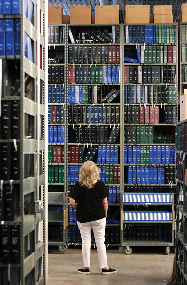 Library employee dwarfed by the stacks at the stares up at the Utah State Library for the Blind warehouse