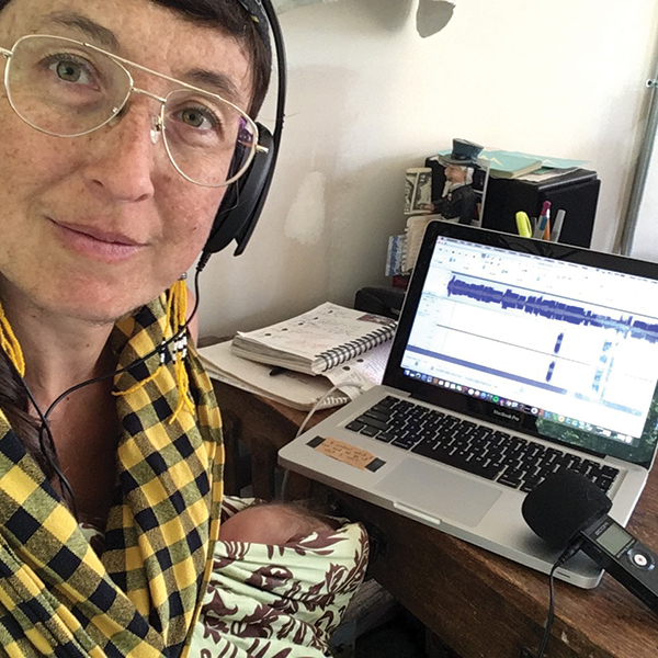 Radio DJ broadcasting at home with her laptop and microphone